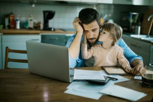 Father reviewing changes to income protection insurance policy on laptop with daughter