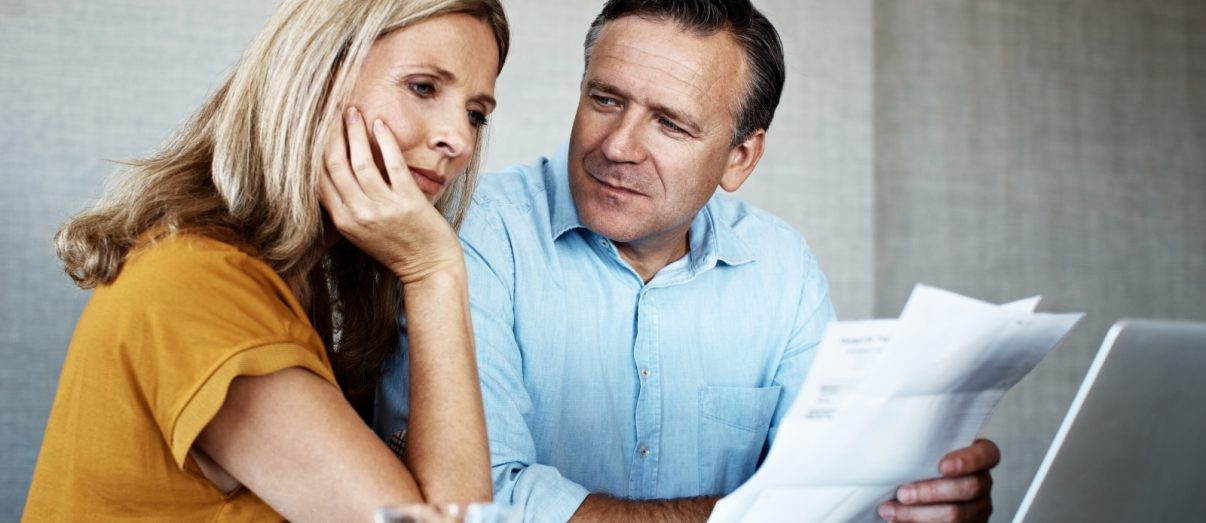 Couple reviewing income protection changes on laptop
