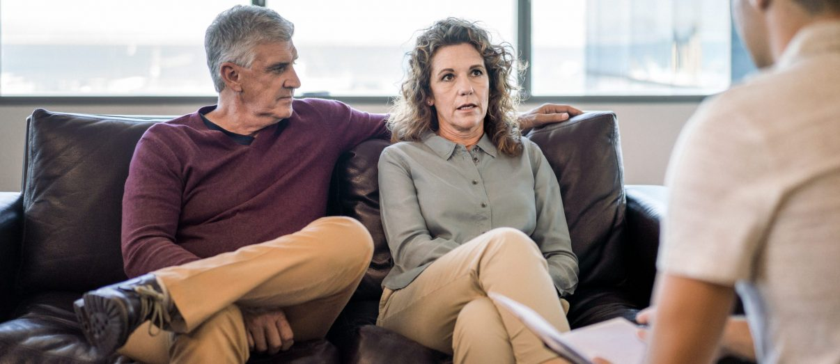 Mental health, financial and matrimonial professional with mature couple at office. Man is looking at woman sitting on psychiatrist's couch. They are wearing casuals.